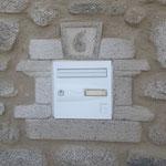 Entourage de la boîte aux lettres en fausse pierre avec le numéro de maison