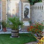 Ribnitz-Damgarten: Putten als Nischenfiguren in mediterran angelegtem Garten.