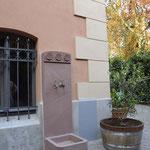 Potsdam: Kleiner Wandbrunnen aus rotem schlesischem Sandstein. Architekturelemente und Ornamente (Rosetten) vom Haus teils aufgenommen. Maßgeschneiderte Steinmetzarbeit.