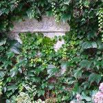 Alzey, Rheinland-Pfalz: Steinrelief VINO, Carrara-Marmor-Guss. Phantasievoller Garten mit liebevollen Arrangements.