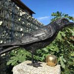 Lutherstadt Wittenberg: Bronzefigur Vogel Rabe PEDRO mit Bronzeobjekt APFEL, gold patiniert