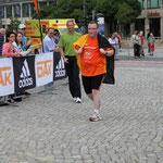 """Einer der Letzten vom 10 km-Lauf erreicht kurz vor dem ersten """"Halbmarathoni"""" das Ziel ..."""