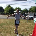 Der Erste Läufer der 13,5 km Strecke kommt ins Ziel ...