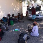 """村の集会所にたむろする人たち。今日は""""Pay Day""""という日で、集会所で手続きすると年金がもらえるとのこと。(クマナ村)"""