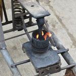 """Arbeitsgerät des """"Vulcanaizer"""" (Kolben eines Verbrennungsmotors zum Heizen). Damit werden Reifen und Schläuche geflickt."""