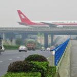 Beim Flughafen Chengdou führt eine Rollbahn über die Strasse.