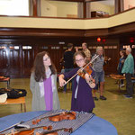 Supporter Deidre Orr looks on as volunteer Samantha Orr tried one of the violins at the Luthier Exhibit.