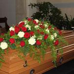 Sargbouquet aus roten und weißen Rosen