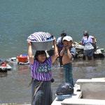 Las mujeres cargan todo en la cabeza. Esta foto es al terminar de lavar ropa en el lago.