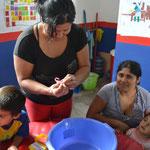 Madres de familia aprendiendo a lavar las manos de manera correcta