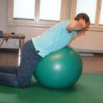Ball: Oberkörper auf den Ball legen und LWS aufrichten