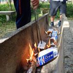 コッペパンをアルミホイルで包み、牛乳パックに入れて火をつけると、焼きたてのパンのよう!
