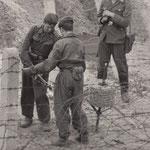 26. September 1961. Bewaffnete Einheiten bewachen die Arbeitstrupps, die die Stacheldrahtzäune verstärken, die Westberliner zerschnitten hatten, um Verwandten und Freunden zur Flucht zu verhelfen