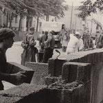 """18. August 1961, bewaffnete Volkspolizisten bewachen Ostberliner Bauarbeiter bei den Arbeiten an der """"Chinesischen Mauer""""."""