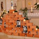 """Die """"Gedenkmauer"""" mit einigen Fotos der """"Sinti-Kinder von Mulfingen"""" und Kerzen für jedes deportierte und ermordete Kind, Foto: Manuel Werner"""