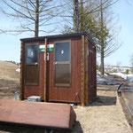 雪解け直後のゴルフ場にある水洗式バイオトイレ