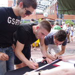 Jordan and friends sign a joint ribbon