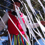 A man on stilts seen through the ribbons.