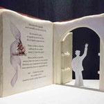 Maquette d'un grand livre ouvert servant de passage à l'entrée d'une partie du parc