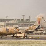 Die Sonne bekämpft den Schneesturm während der Airbus A330-243 von Air China (B-6076) enteist wird