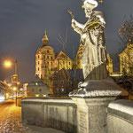 Brückenfigur auf der Elisenbrücke mit Blick auf das Schloss (Johann-Nepomuk-Statue)