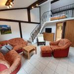 Studio Wohnzimmer mit Couch, Aufgang obere Etage mit Schlafzimmer 1 und 2