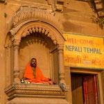 Assis en position du lotus, un homme médite face au soleil qui se lève sur le Gange