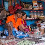 Couple de commerçants dans leur minuscule boutique visionnant une série sur leur smartphone