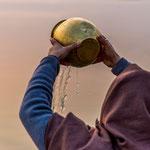Cette femme verse l'eau du Gange en offrande au soleil