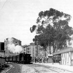 1890 Llegada del tren a la primera Estación de la Costa, al sur de la Avenida de Alfonso XIII. Esta estación fue incendiada en 1902, tras lo que se construyó una nueva en Calderón de la Barca. Detrás, comienzo de Méndez Núñez