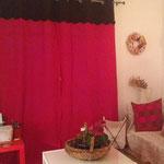 Rideaux rouges et brun réalisés à partir d'un dessus de lit.