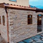 """Naturstein""""Mauer"""" nach Kundenwunsch, mit Segmentbögen und eisernen Fenstern."""