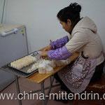 Eine Frau macht chinesische Maultaschen (饺子 - jiao3 zi5), die dann später gekocht oder gebraten verkauft werden.
