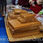 Das ist wirklich schwer zu erklären. Vor allem zum Frühlingsfest ist das in Süd-Fujian eine Spezialität. Es ist ein gummiartiger Kuchen, der aus Klebreis unter Beimischung von verschiedenen Zutaten gemacht wird - süß oder salzig. Kann aufgewärmt werden.