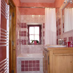 La salle de bains avec carrelages fait main, baignoire, wc.