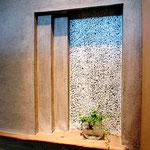 白セメントを使って洗い出しで仕上げたかざり棚。棚板は流木を使用。