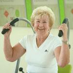 Ältere Frau trainiert an einem Rücken College Gerät und lacht