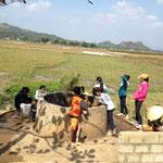 Frauen beim Schöpfen vom Wasser aus einem Brunnen