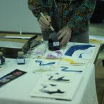 Démonstration de calligraphie avec les encres exposées sur le stand