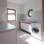 Hauswirtschaftsraum neben der Küche mit Doppelspüle und Waschtrockner