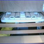 Betthälfte hoch geklappt. Der Tisch wird eingeschobenen, das Schuhregal ist erkennbar. Als Trennwand dienen Latten eines alten Sprungrahmens die mit Zwischenstücke in 2 U-Schienen eingeschoben werden.