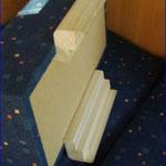 Das ist der Keil, der zwischen den Vordersitzen eingesetzt wird. Die Schienen liegen auf den Bügeln, an denen man die Sitze verschieben kann.