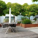 Die Terrasse ist gekonnte vielseitig gegliedert, bepflanzt und materialisiert (Bodenbeläge in Zementplatten, Holz, Kies)