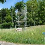 Ein Gerüstturm auf dem Baugrundstück zeigt die Geschoss-Niveaus des fertigen Baus an.