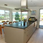 Blick über die sehr grosszügig konzipierte Küche hinweg zum Essbereich mit herrlicher Aussicht