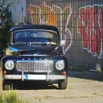 Volvo Buckel mit Graffiti im Hintergrund.