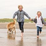 Kinder mit Hund laufen am Strand-Fotografie Annett Mirsberger