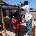Die Sonne brennt, im kleinen Haus gibt's wenig PLatz. Deshalb lassen wir ein in Kenia uebliches Vordach anbringen, unter dem die Kinder sitzen und spielen koennen.