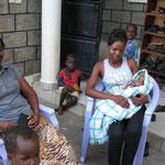 Links Josephine, die schweren Herzens Baby Terriana an die Pflegemama rechts übergibt.