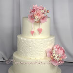 Weiße Spitze mit rosa (Zucker-)Blumengestecken